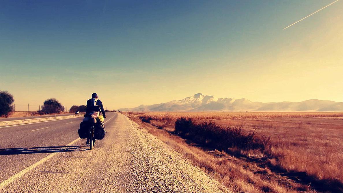 Radfahrer auf einer einsamen Straße (Normadic Kitchen)